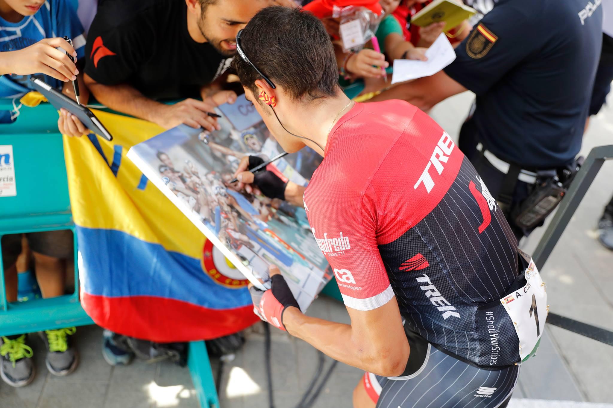 Alberto Contador firmando un poster con su victoria en Fuente De